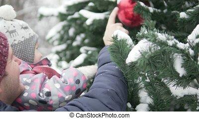 Dad shows daughter elegant Christmas tree.