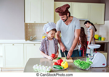 Dad shows his son how to cut vegetables right. Gir works with her mom behind boy close to stowe. Family is preparing breakfast together.