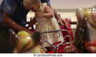 Dad takes his daughter from the toy chariot