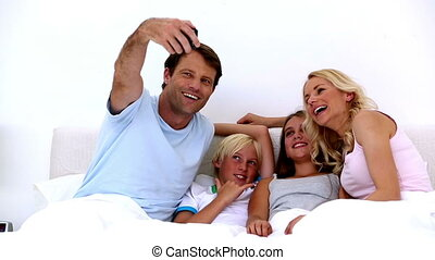 Dad taking a photo of him and family at home in bed