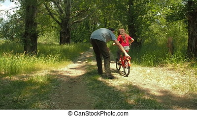 Dad teaches her daughter to ride a bicycle.