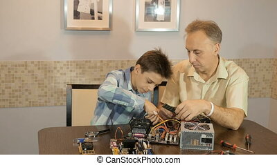 Dad teaches his son a teenager, what's inside the computer. RAM.