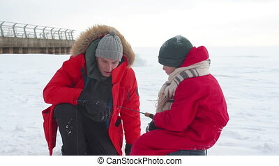 A man and his son are fishing together on a frozen lake