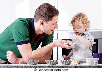 Dad teaches son bake muffins