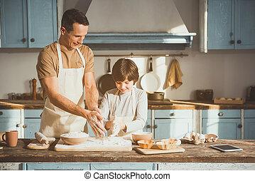 Dad teaching child making pastry