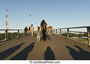 dad, the man with 2 two children, daughter and son, people are on the bridge in the sun