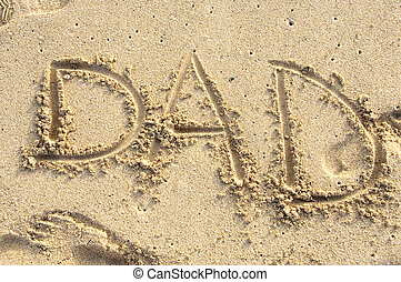 Dad - the word DAD spelled out in the sand at the beach in...