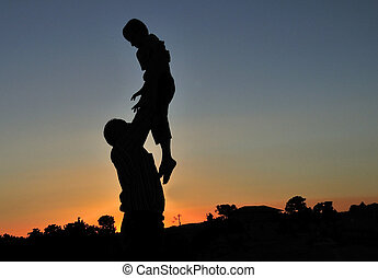 Dad throws the child at sunset
