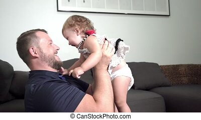 Dad turns and throws up a small daughter on hands in the Sunny living room