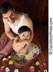 Dad washing small baby girl