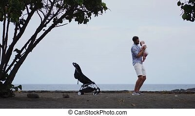 Dad with a baby on the beach with a stroller