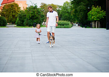 Dad with a little daughter walking a dog in the park.
