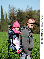Dad with a small child walking on green meadow