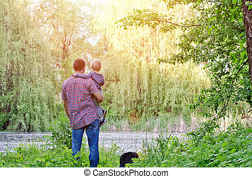Dad with a small son are standing on the shore of a forest lake, rear view