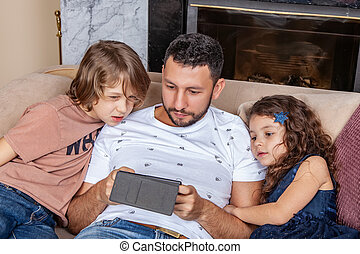 Dad with children watching videos on a smartphone