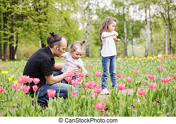 Dad with daughters among tulips