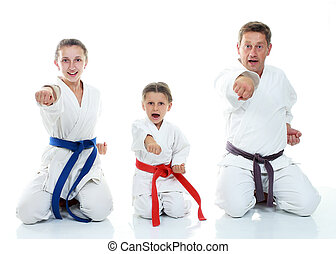 Dad with daughters in a ritual pose karate and beat his fist