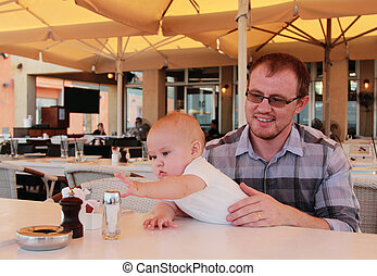 Dad with his baby daughter in a cafe ordering breakfast