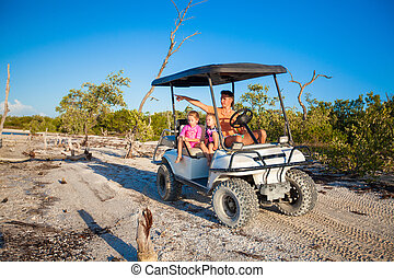 Dad with his two daughters driving golf cart at tropical beach