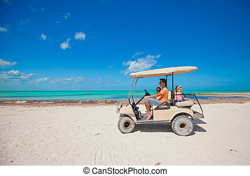 Dad with his two daughters driving golf cart at tropical country