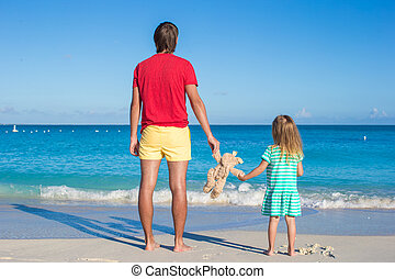 Dad with little baby holding a plush toy on exotic beach