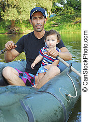 Dad with little daughter sitting in a boat on the river.