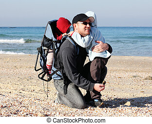 Dad with two children walk along the sea