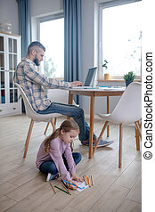 Dad working at the table, daughter sitting on the floor.