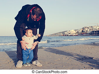 Daddy and baby boy on the sandy beach autumn