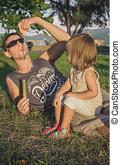 daddy and daughter blowing a bubbles in the park