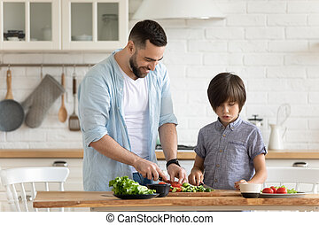 Daddy and little son preparing vegetable salad together in ...