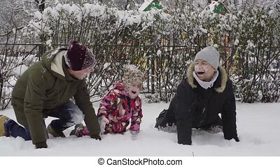Daddy and uncle fooling around with daughter in the snow.