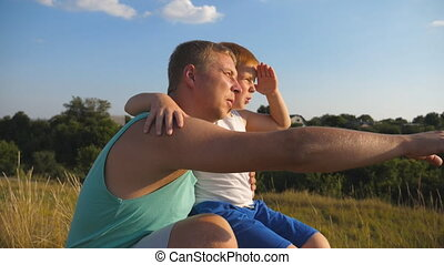 Daddy pointing at something to his little kid. Dad and child sitting at green grass on the hill and speaking with each other. Father with his little son spending time together outdoor. Slow motion