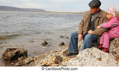 daddy with daughter sit on stone on river bank