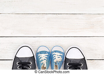 Daddy's boots and baby's sneakers, on white wooden background, father's day concept.