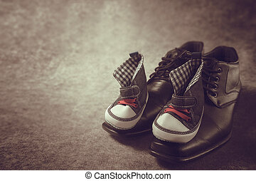 Daddy's boots and baby's sneakers, on wood background, fathers day concept. vintage color
