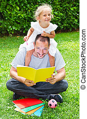 Dady reading a book to his daughter