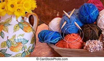 Italian Pitcher full of daffodills next to a antique wooden bowl full of yarn and knitting needles