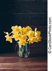 daffodils in a glass vase on a wooden background, spring bouquet