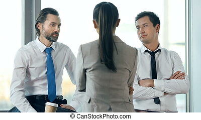 Daily Briefing - Business team of three having a briefing at...