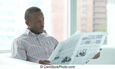 Daily news - Serious African-American man looking through...