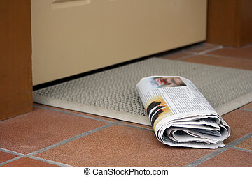 Daily newspaper waiting to be picked up outside home...