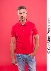 Daily outfit. Man looks handsome in casual shirt. Guy with bristle wear casual outfit. Man model clothes shop. Menswear and fashionable clothing. Man calm face posing confidently red background