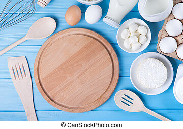 Dairy products on blue wooden table. Sour cream, milk, cheese, egg,  and butter.