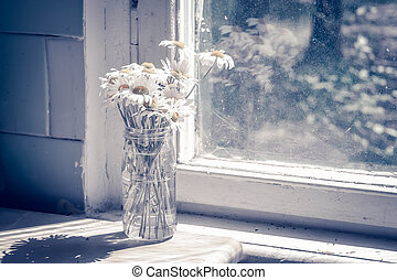 daisies in bouquet in vase on table with window