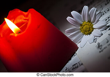 Daisy and Red Candle on Music Notes Sheet