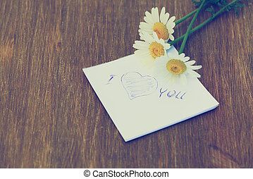 "Daisy flower and piece of paper with text "" I love you"" on the wooden table. Photo in vintage style"