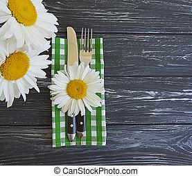 daisy flower fork knife on wooden background