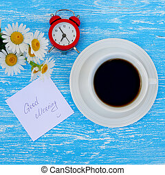 Daisy flowers, alarm clock and cup of coffee with good morning note on rustic blue wooden background
