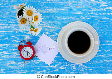 Daisy flowers, alarm clock and cup of coffee with I love you note on rustic blue wooden background